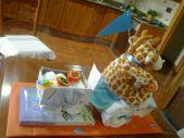 Triciclo con jirafa de peluche con pañales.